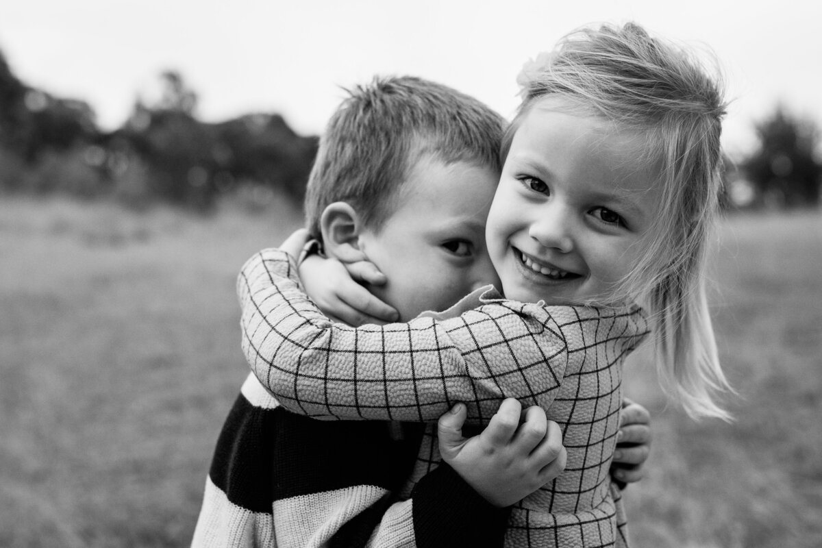 black and white siblings hugging Melbourne outdoor family photographer And So I Don't Forget Photography