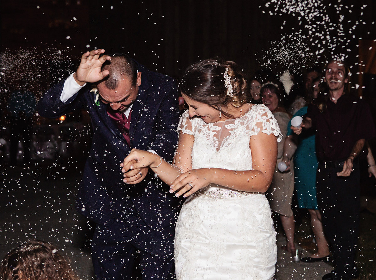 bride and groom duck as rice is thrown at them during their wedding exit at The Barn at TH Farm