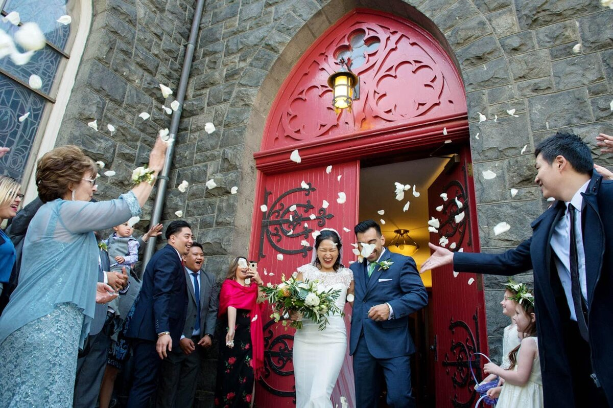 guests toss flowers on a bride and groom as they exit a bright red door of a cathedral