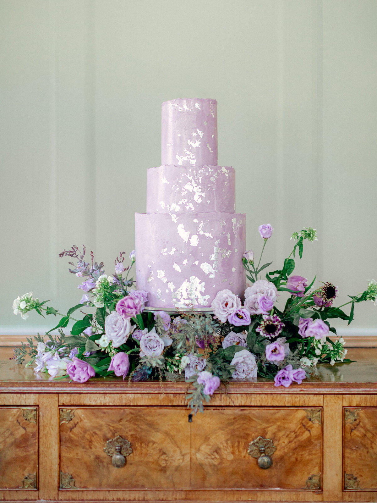 purple three tiered cake surrounded by purple florals