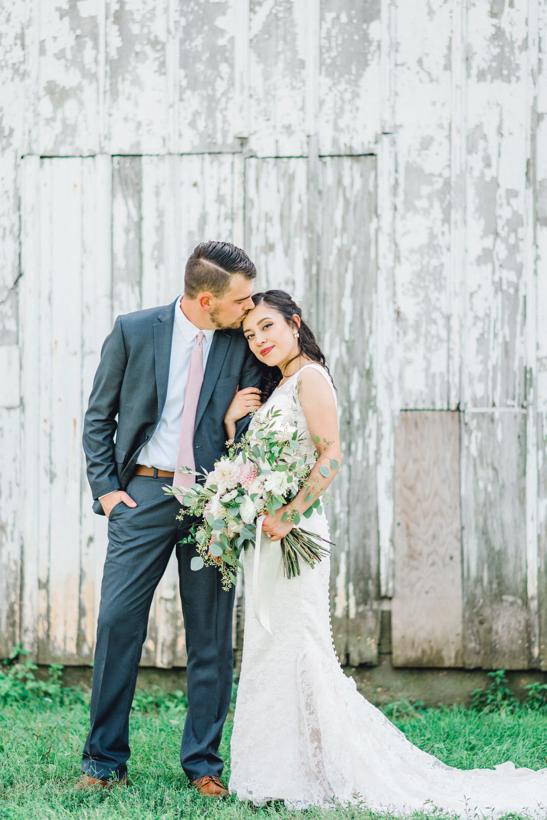 groom kissing bride in front of white barn