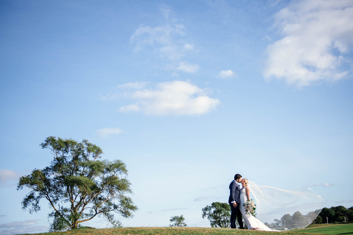 bride and groom kissing on the golf course for wedding at the Mansion at Timber Point