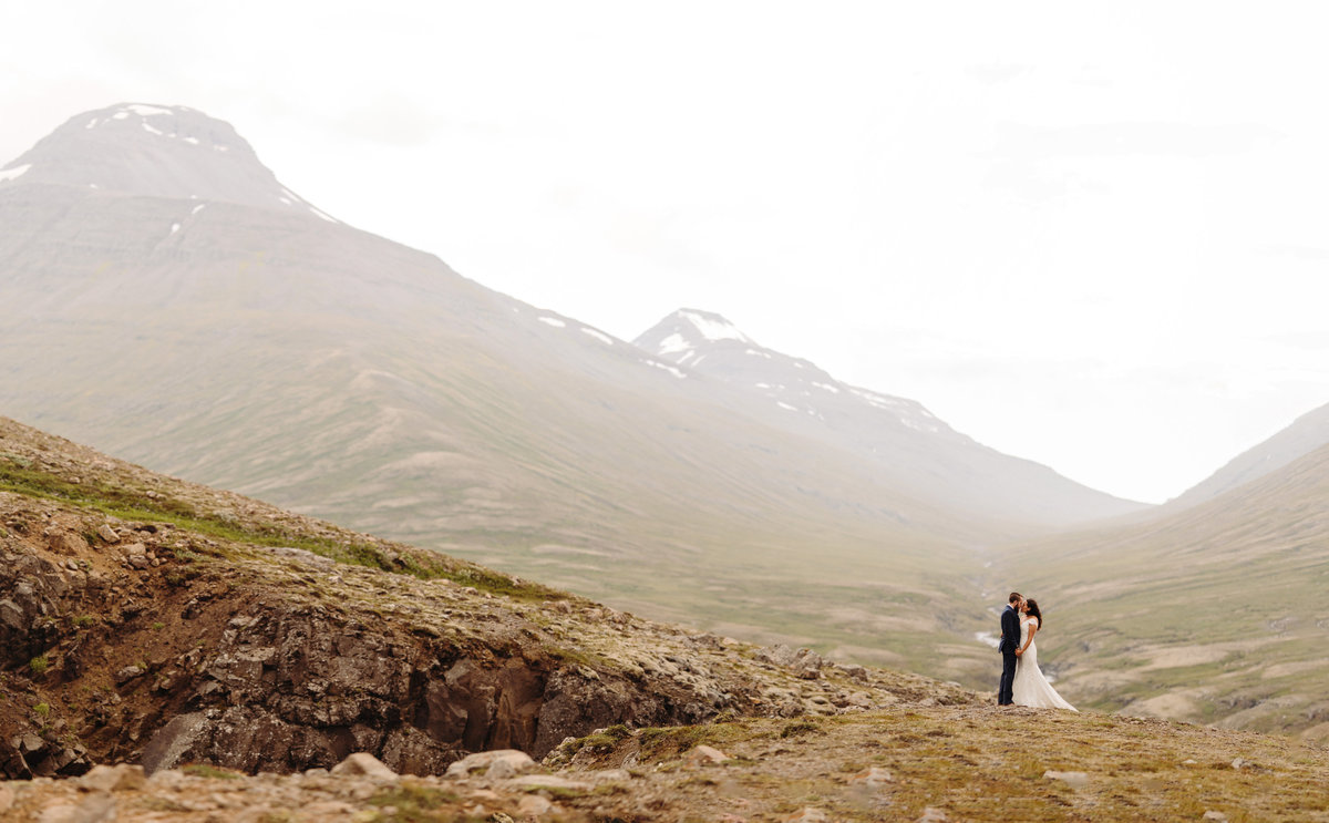 Bride & groom embrace in a valley after their Iceland wedding.