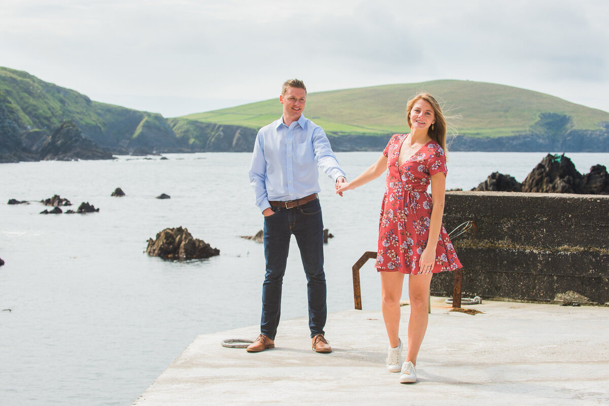 young couple in summer dress holding hands while standing on a pier