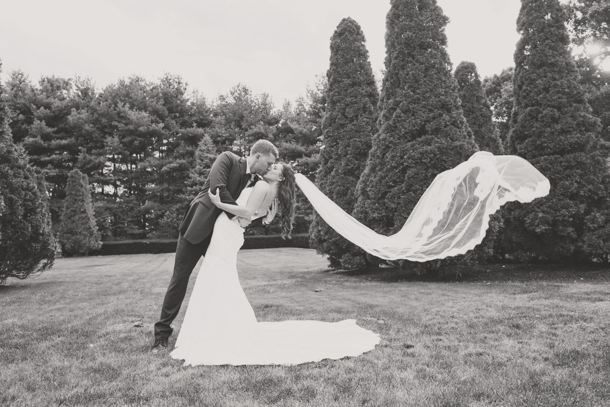 black and white photo of bride and groom shot outside with veil flowing from wedding reception at The Carltun