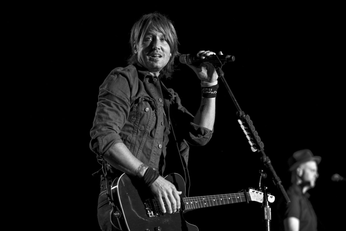 Keith Urban holding microphone in black and white