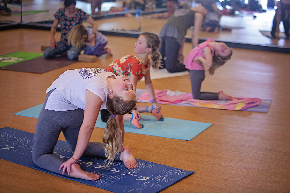 Teen girl practices camel pose in yoga class