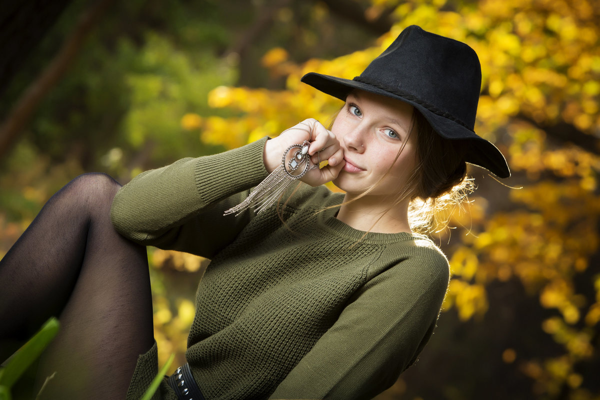 Dan Elliott Photography senior session black hat girl sits with necklace
