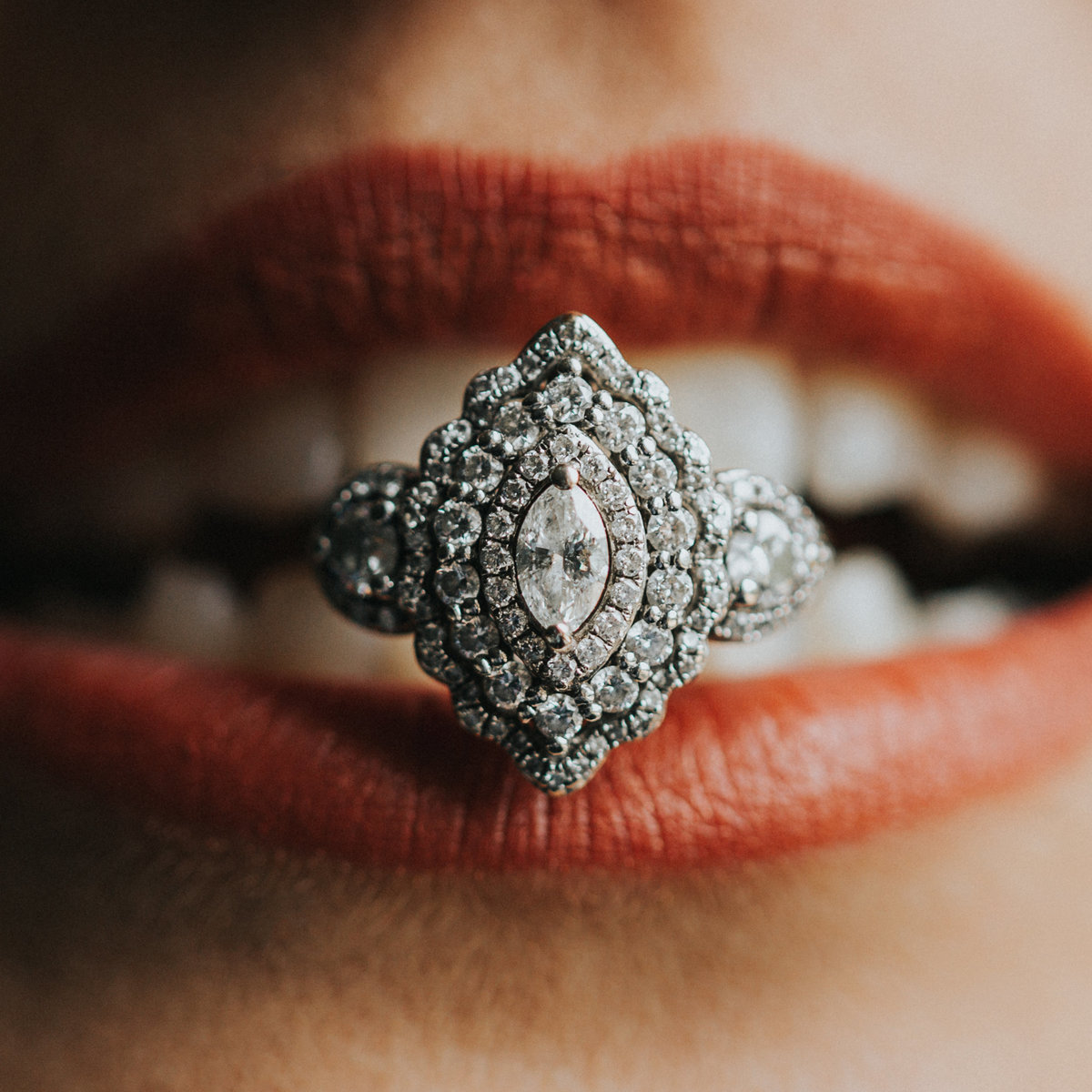 A bride holds her unique wedding ring between her teeth