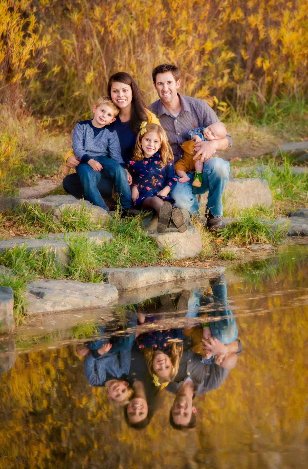 A reflection picture of a family sitting together next to the Laramie River in the fall.