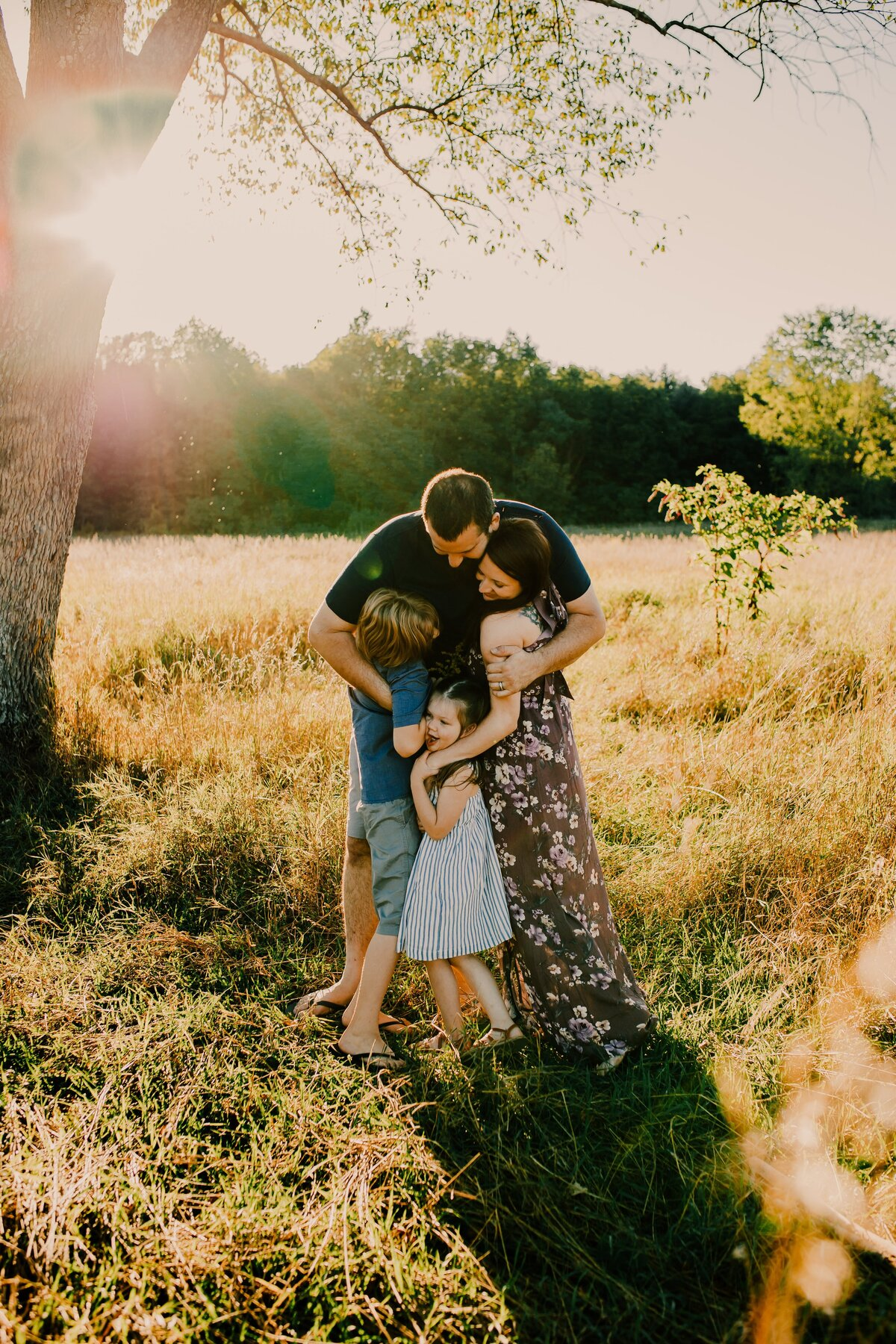 family hugging in a field with sunflare