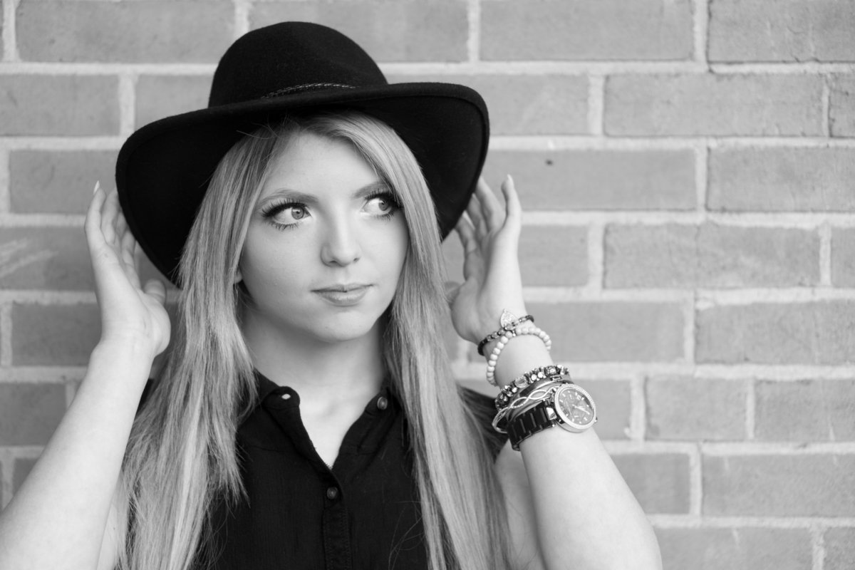 Girl with long blonde hair and a black cowboy hat stands in front of a brick wall