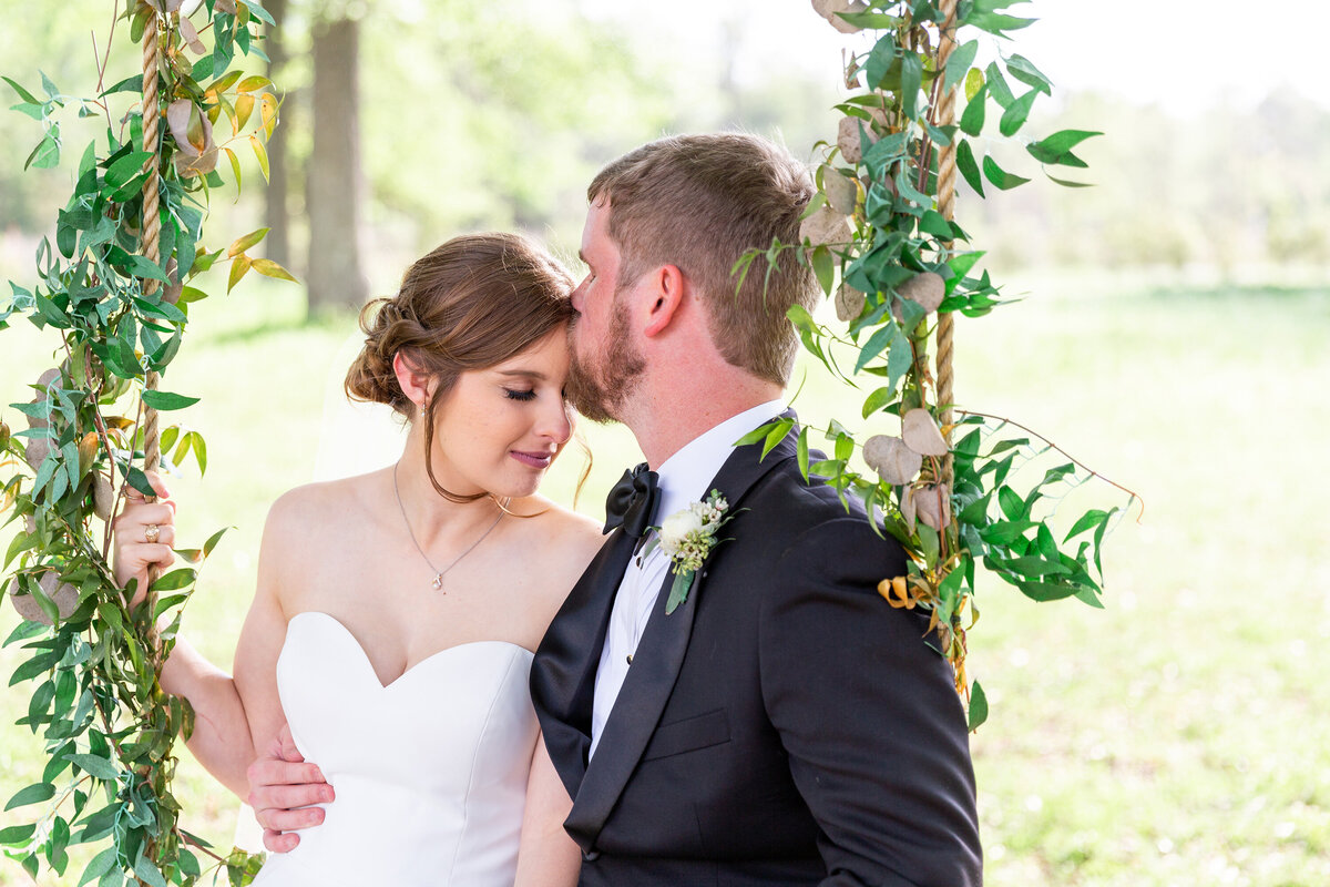 Groom Kisses Bride's Forehead While Swinging Together