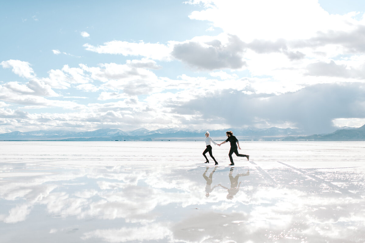 man and woman holding hands while running