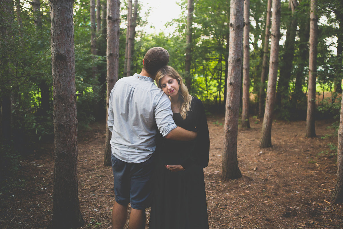 pregnant couple hugging amongst tall trees in forest {Etobicoke Maternity Photographer}