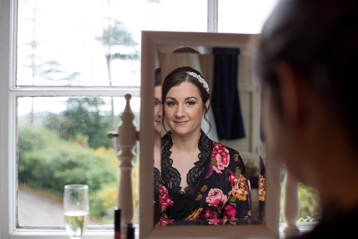 bride in mirror at horn of plenty wedding devon