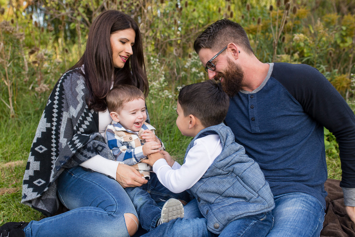 Family of four tickling baby brother outdoors  {Oakville Family Photographer}