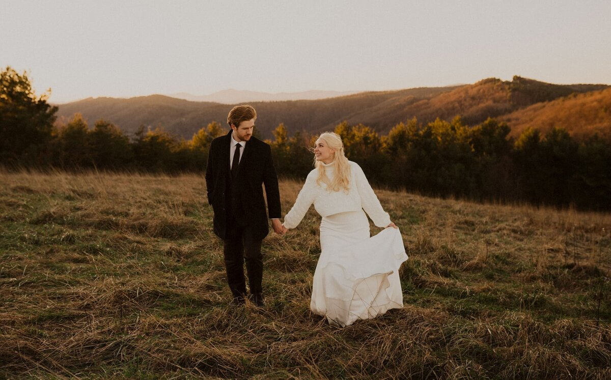 Bride and groom holding hands walking on a mountain