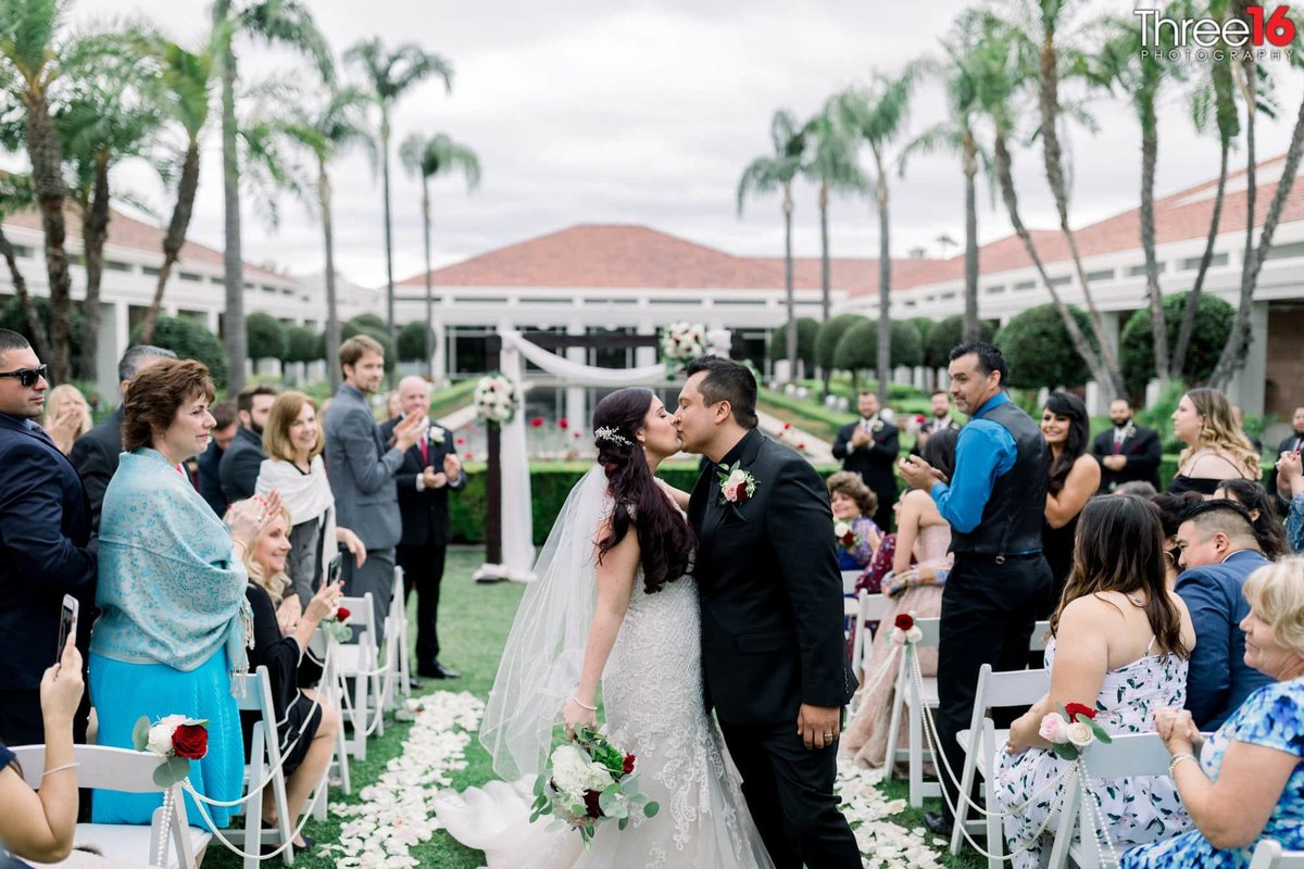 Bride and Groom stop on the aisle for a second kiss