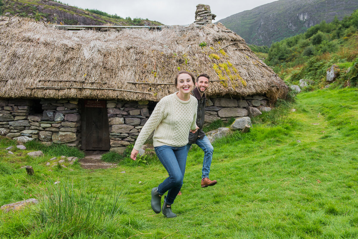 Young couple in aran sweater and denim, holding hands, laughing and running away from thatched cottage