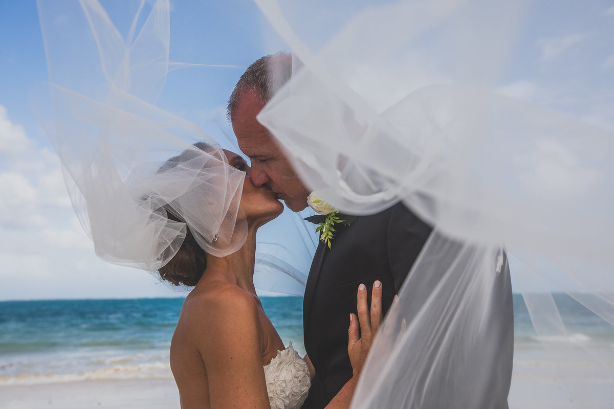 bride kissing her husband under her veil at beach in mexico