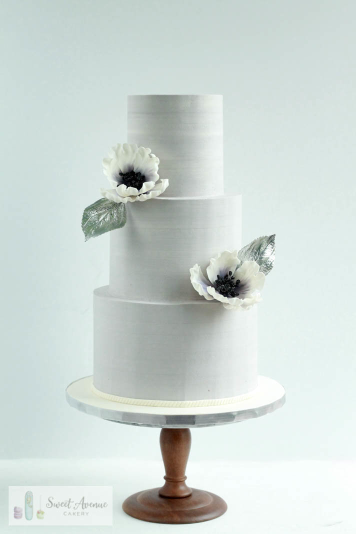 grey buttercream wedding cake with sugar anemones