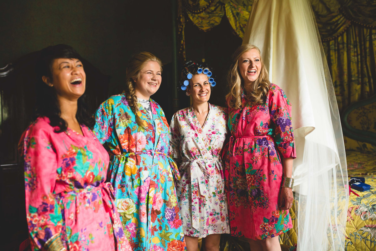bridesmaids in colourful flowery gowns laughing with bride at sezincote house