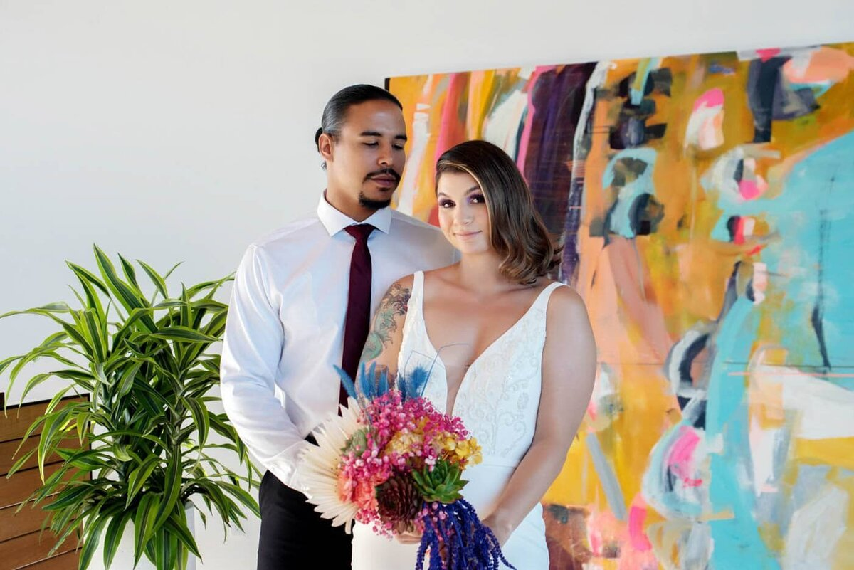a bride and groom holding a very colorful bouquet stand in front of a vibrant mural by therese murdza