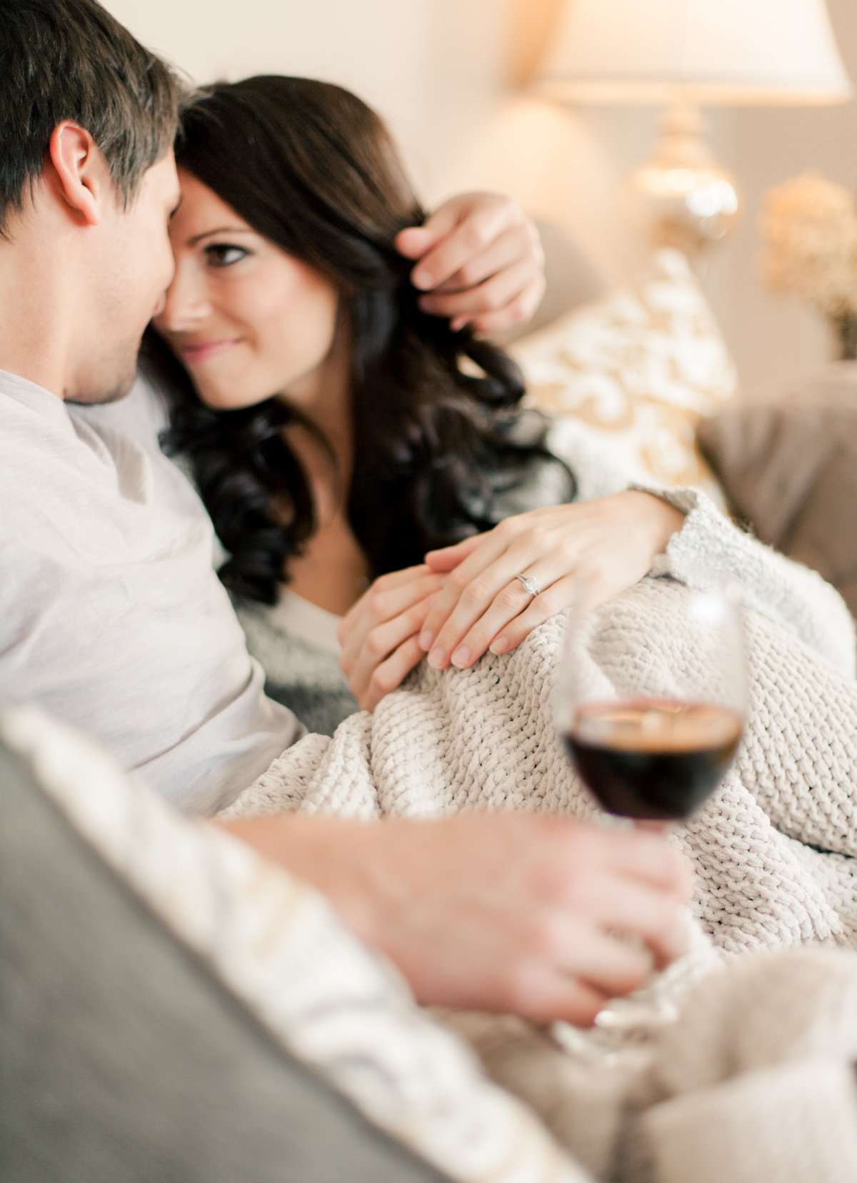 fiances hold wine and cuddle on the couch in rochester minnesota home for engagement photography