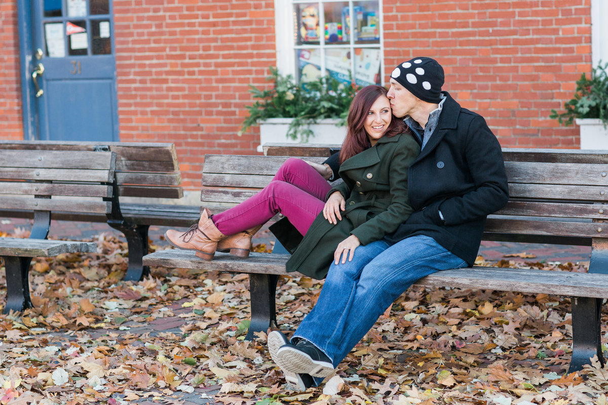 Fall and bricks serve as a backdrop for this kissing couple on a bench in Newburyport MA