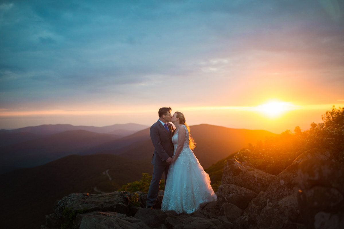 Photo of bride and groom kissing at sunrise over Stony Man Summit.