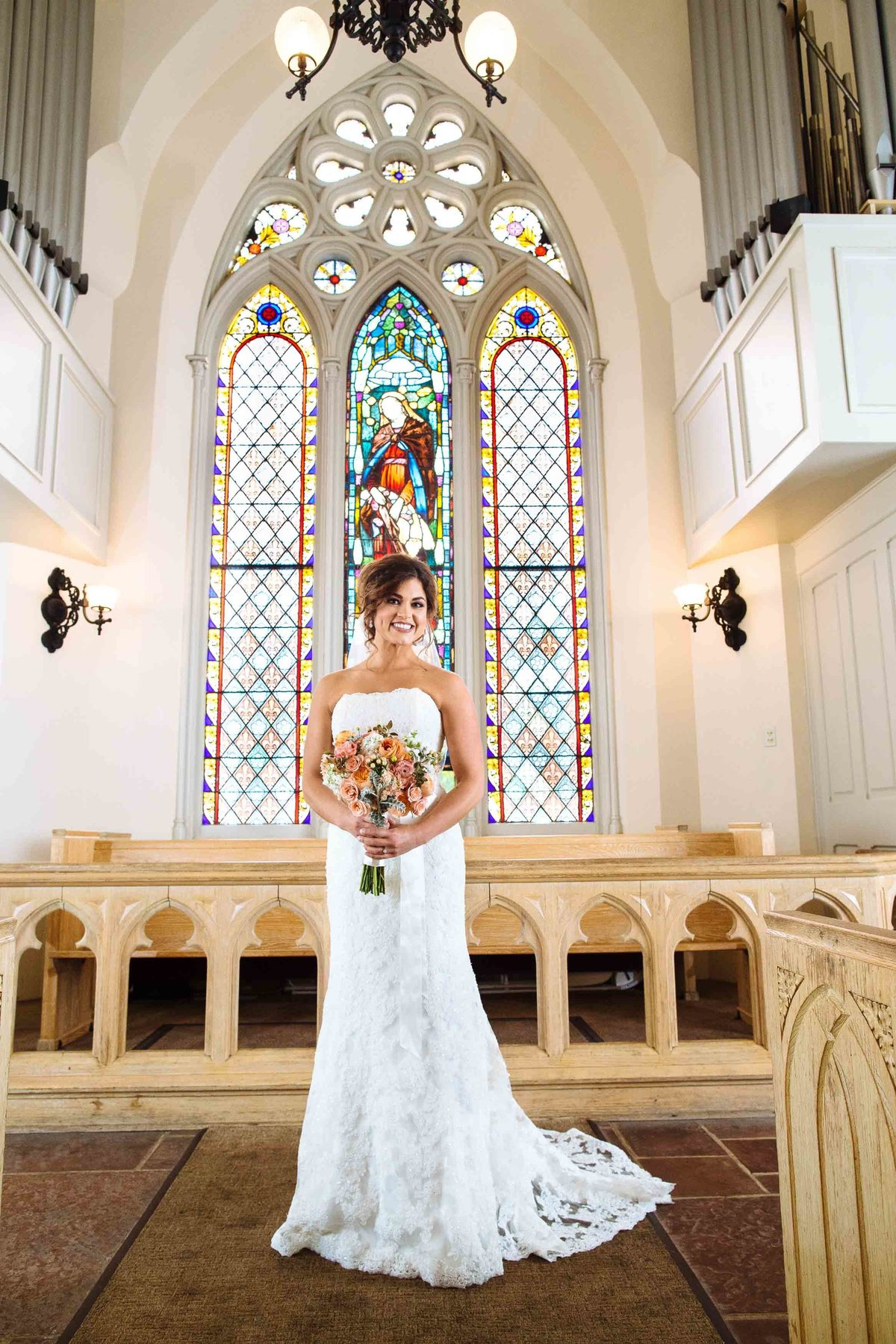 A bride standing inside a church with stained glass windows in the background.