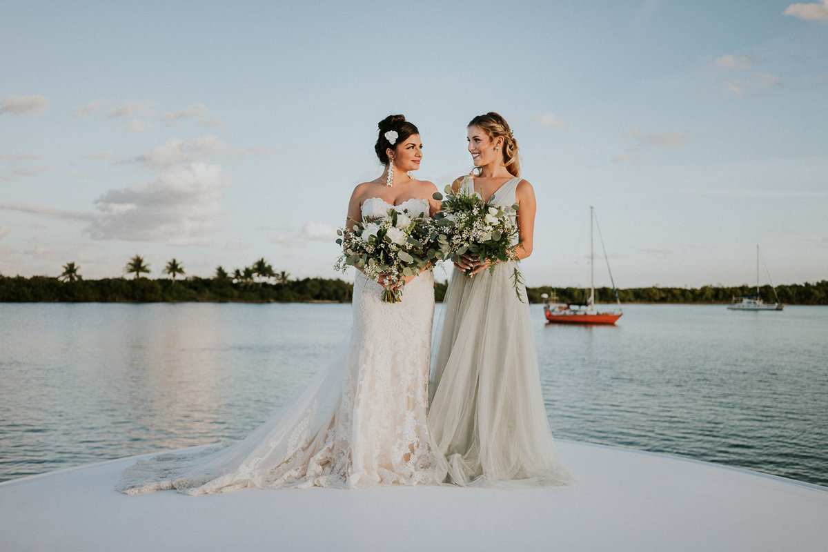 Two brides holding white and green bouquets stand on bow of a yacht on the water for Stuart FL elopement