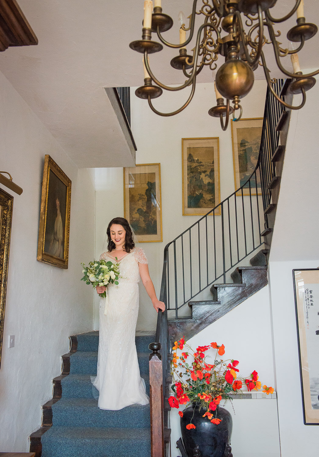 bride wearing a vintage, beaded wedding dress with sleeves walking down the stairs with blue carpet while holding a white flower bouquet