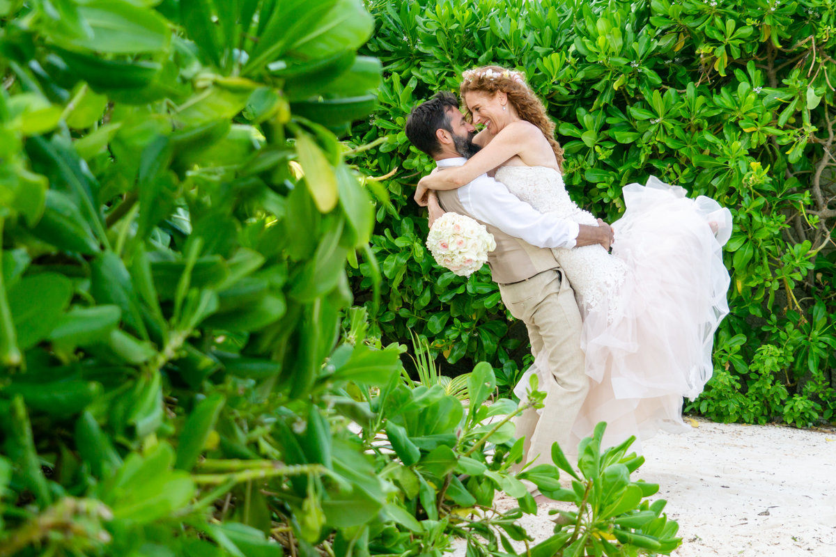Groom holding wife with her feet kicked back in front of green bushes in Playa del Carmen