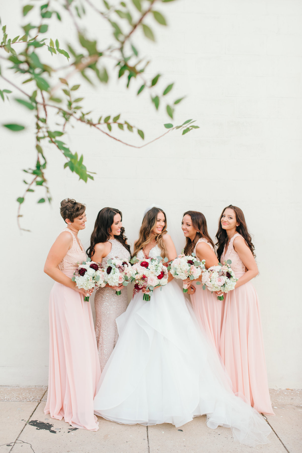 Bride and bridesmaids together smiling
