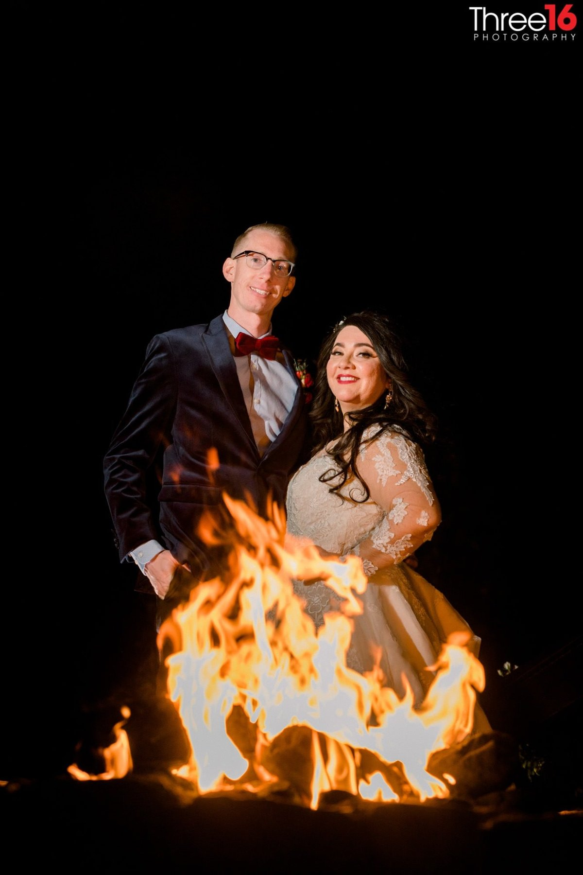 Bride and Groom pose behind a lit up fire pit