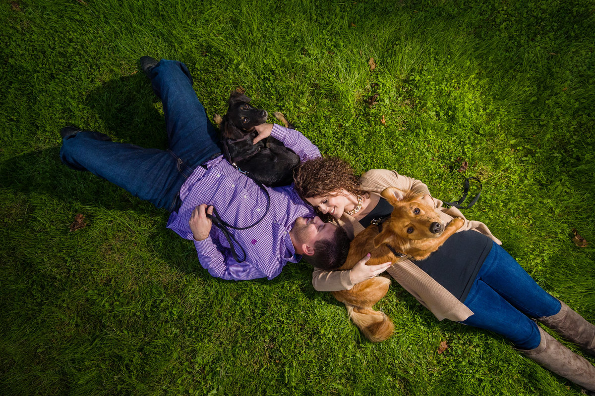 Engagement Photo of couple laying in grass with dogs