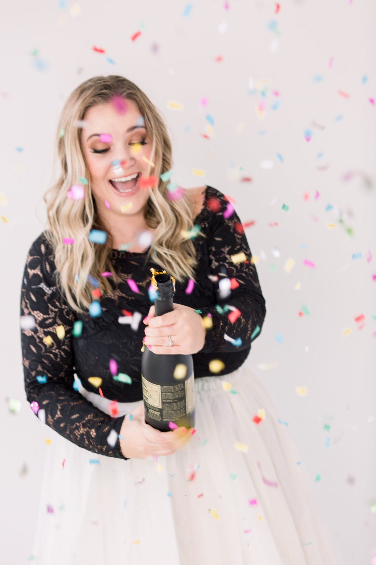 Woman popping bottle of champagne with confetti