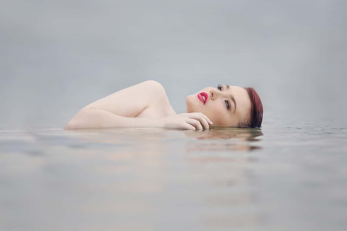 Nude woman in the water wearing red lipstick