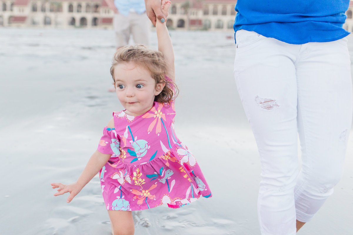 Jacksonville Family Photographer captured an image of a little girl holding her moms hand as she skips down the beach toward the water
