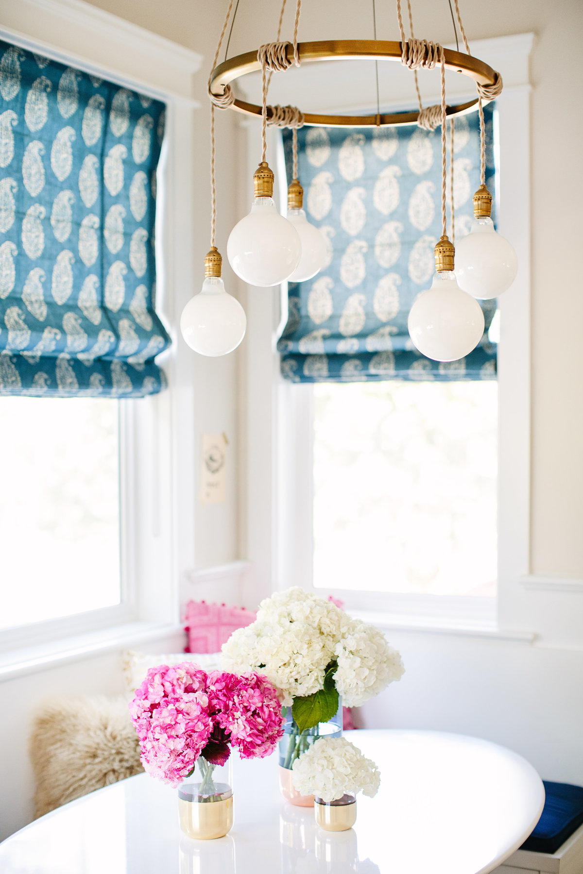 Pink and Navy kitchen breakfast nook with white tulip table, and Eddy chandelier
