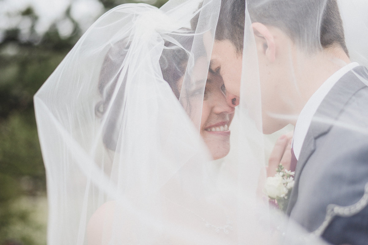 bride and groom under veil together