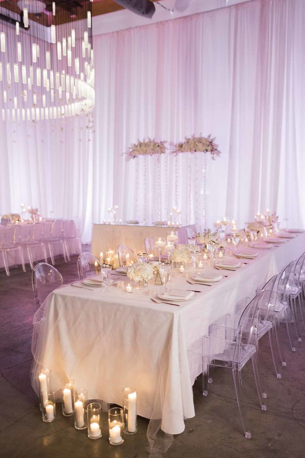 All white wedding with white draping, white linens, white flowers, and lots of candles at Canva Event Space in Seattle