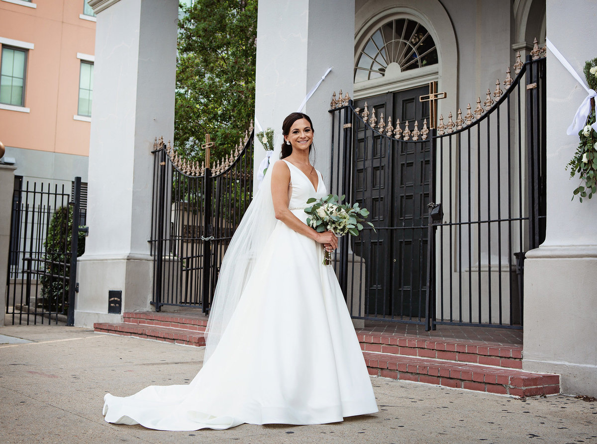 bride with bouquet in front of Our Lady of Guadalupe Chapel in New Orleans