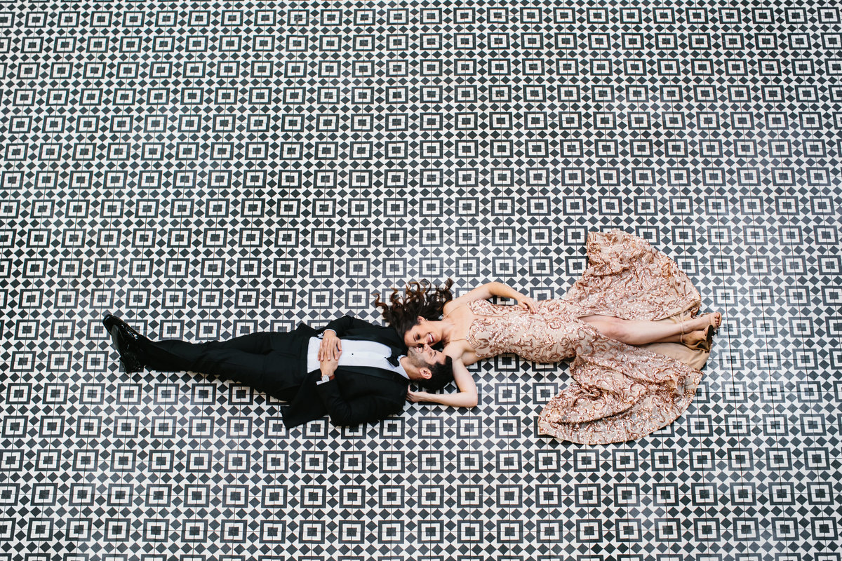A couple in glamorous clothes laying on a black and white patterned tile photographed from above