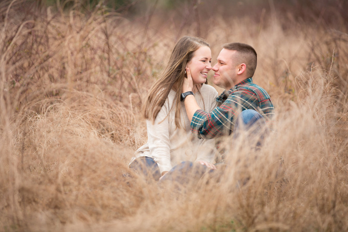 engaged couple looking into each others eyes in fall time for photo