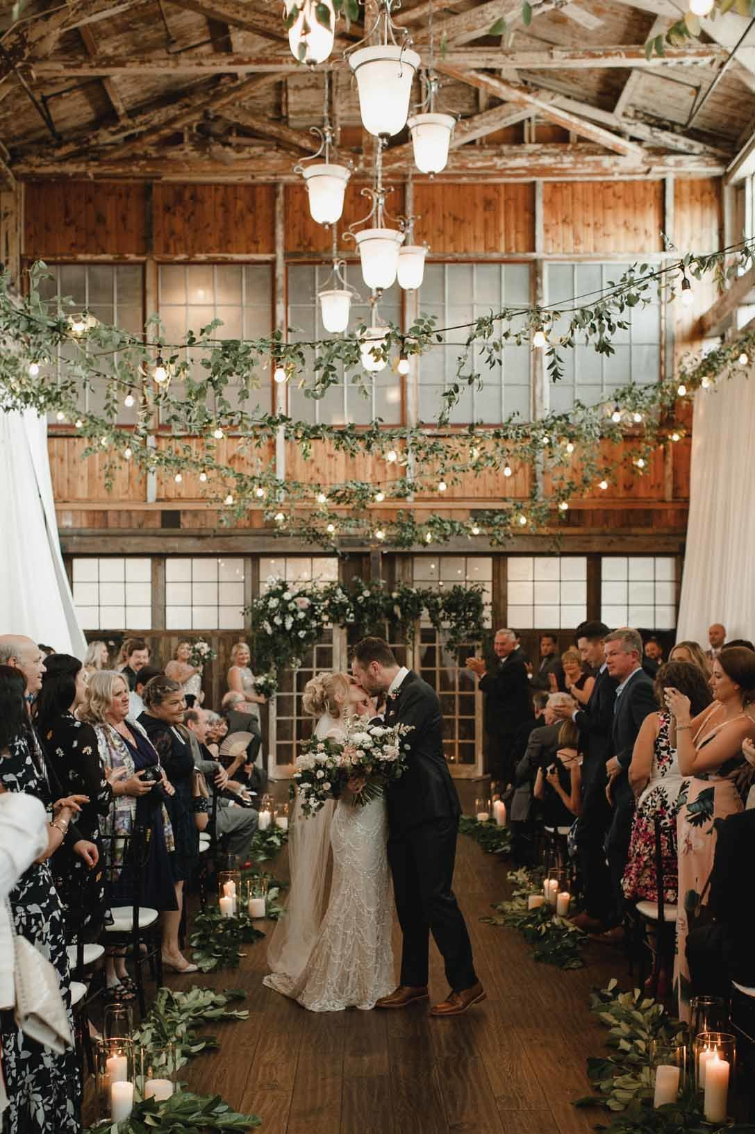 Romantic wedding ceremony space filled with green and candlelight perfectly frame our bride and groom.