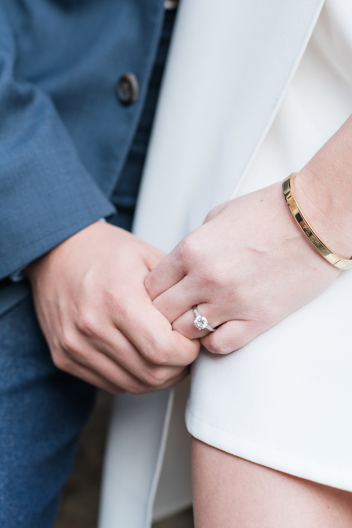 a close up photograph of a circle cut engagement ring with a bride wearing a white dress and a groom wearing navy suit in Saxapahaw NC