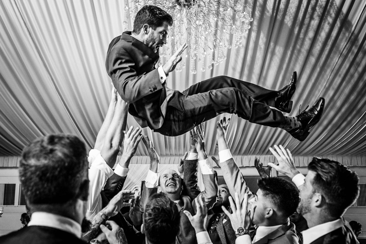 A groom is thrown in the air during a reception at a Gallery Marchetti wedding in Chicago.